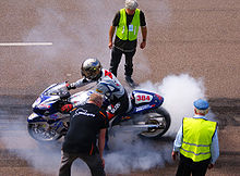 A silver and blue sport motorcycle with racing numbers and covered sponsor logos. The rider has a reflective helmet and wears brightly colored leathers also covered with logos. His hands on the clutch and brake levers while the front wheel does not turn and the rear wheel spins and emits a cloud of white smoke. Three officials stand close by and observe.