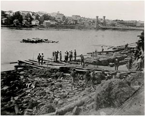 Hennepin Island tunnel - Photo taken shortly after the Hennepin Island tunnel collapse. The scene is of a group of men sorting logs on Nicollet Island looking toward St. Anthony Falls. A barge is visible in foreground and Minneapolis buildings are in the background.