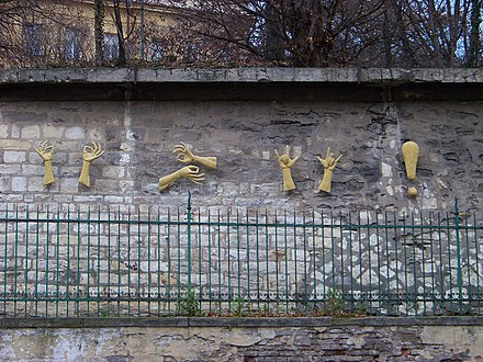 "Sign language relief sculpture on a stone wall: ""Life is beautiful, be happy and love each other"", by Czech sculptor Zuzana Čížková on Holečkova Street in Prague-Smíchov, by a school for the deaf"