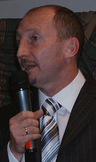 A man wearing a shirt, tie and jacket; holding a microphone.