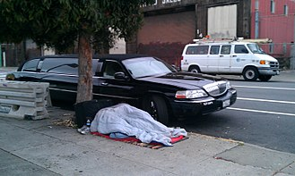 California housing shortage - A homeless person sleeps on the sidewalk next to a limousine in the Mission area of San Francisco.