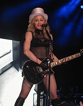 Madonna playing electric guitar in front of a microphone