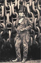 A 19th-century man wearing jacket trousers and waistcoat, hands in pockets, cigar in mouth, wearing a tall stovepipe top hat, standing in front of giant iron chains on a drum.