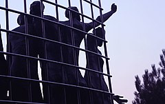 Close-up of sculpted human figures reaching through the fence