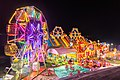Illuminated Ferris wheel, bouncing castle and carousel at night in a funfair in Vientiane, Laos.jpg