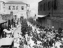 In a black and white photograph, a large group of turbaned men on horseback ride through a dusty, sunlit street and into the distance, obscured by dust. A crown of civilians watch the men pass. A large, brick-built, two-storey building is on the left, and a similar structure is on the right.