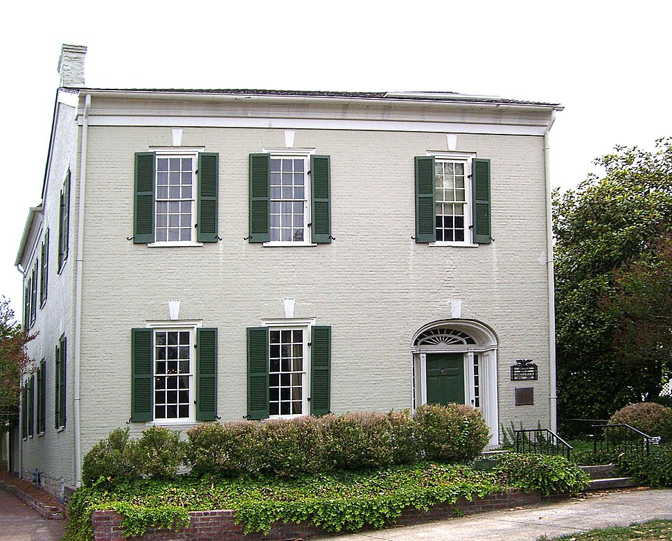 A two-story brick building with large windows and shrubbery in front of it