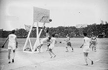 Deux équipes disputant un match de basket-ball sur un terrain en extérieur.