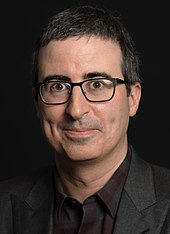 Headshot of comedian John Oliver, wearing a suit and glasses