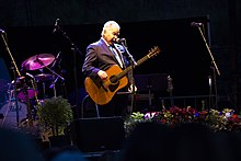 Prine onstage with a guitar and a microphone