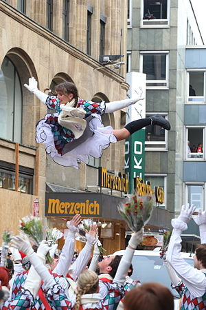 "Majorette (dancer) - A Funkemariechen (ger. diminutive for ""Glistering Mary"") majorette is lifted at Rose Monday Parade of the Cologne Carnival in Germany"