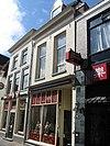 Pand met geverfde lijstgevel, dakkapel en jongere winkelpui
