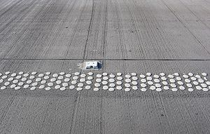 "Road surface marking - White raised pavement marker near ""pea-structure"" side-line on highway surface"