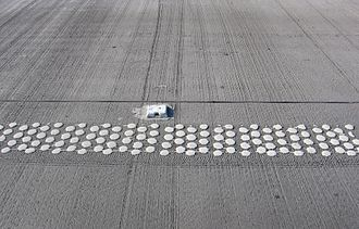 """Road surface marking - White raised pavement marker near """"pea-structure"""" side-line on highway surface"""