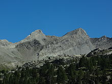 Two barren, grey granite peaks rising from a ridge, against the blue sky