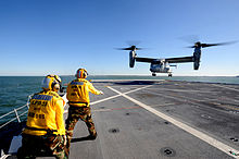 A V-22 performing a vertical landing on USS New York with two of the ship's crew nearby.