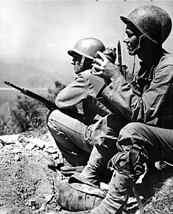 Two men in military uniforms standing on a ledge overlooking a river