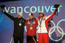 Three young men dressed in winter clothing stand embraced side-by-side in front of a wall with the Olympic rings and the word Vancouver. The man on the center carries a gold medal around his neck, while the two men on the left and on the right carry a silver and a bronze medal, respectively, and hold up a flower bouquet.