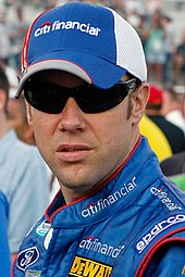 A head and shoulders portrait of a man in his late thirties. He is wearing black sunglasses and facing near to the camera. He is wearing a blue and white baseball cap which displays the CitiFinancial logo at the front. He is also wearing blue racing overalls, upon the collar which the CitiFinancial is embroidered and on the shoulders and body. Logos for Ford, DeWalt and Sparco are also displayed.