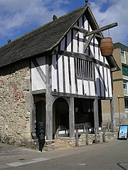 A photograph of a medieval building with white rendering and plain woodwork; a barrel is hung above the entrance and a small visitor's sign is placed on the street alongside the building.