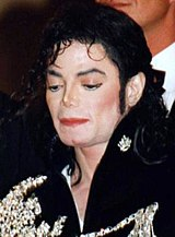 A man with long dark hair wears a jacket with an elaborate silver adornment. Rouge and other makeup is applied to his light skin. He looks pensively in front.