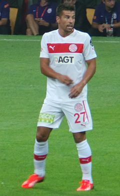 Photograph o a player in a white fitbaw kit standin on grass