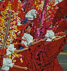 Women in elaborate dresses covered in flowers