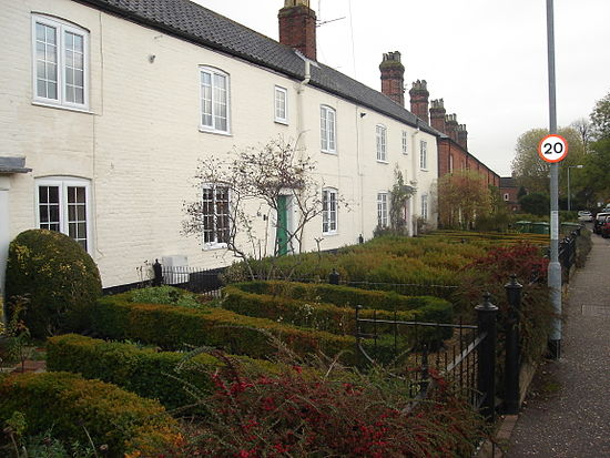 The densely planted front gardens of terrace cottages in Norfolk, England.