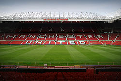 "A stand of a football stadium. The seats are red, and the words ""Manchester United"" are written in white seats. The roof of the stand is supported by a cantilever structure. On the lip of the roof, it reads ""Old Trafford Manchester""."