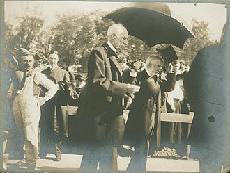 Goldwin Smith - Goldwin Smith (center) and Andrew Dickson White (behind him, with top hat) at the opening of Goldwin Smith Hall, 1906.