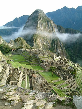 Huayna Picchu - Sunrise over Huayna Picchu towering above the ruins of Machu Picchu
