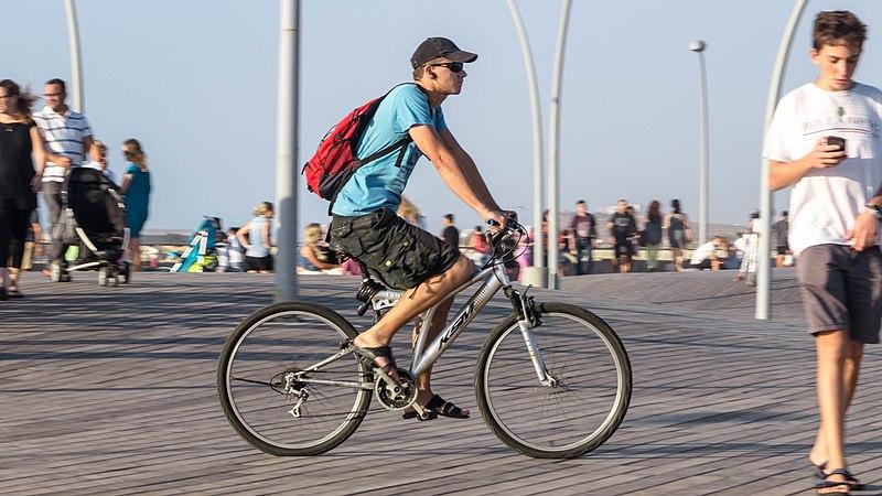 גבר רוכב על אופניים בטיילת