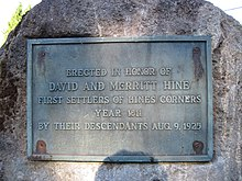 "Cast metal plaque bolted to a bolder, showing clear signs of age. The plaque reads, ""ERECTED IN HONOR OF/DAVID AND MERRITT HINE/FIRST SETTLERS OF HINES CONRERS/YEAR 1811/BY THEIR DESCENDANTS AUG. 9, 1925."""