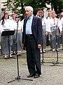 Politoloog Rein Taagepera esinemas Eesti taasiseseisvumispäeva puhul Tartu vabadussamba ees, tema taga naiskoor Emajõe Laulikud, 20. august 2012.jpg