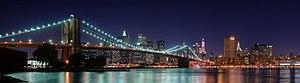 Een helder verlichte stad bij nacht.  Een hangbrug verlicht met heldere blauwe lichten kruist een stilstaand lichaam van water in de voorkant van de stad.  Het water reflecteert het blauwe licht, waardoor de regenboog-achtige strepen op het oppervlak te verschijnen waar de lichten van de brug en de stad samenkomen.
