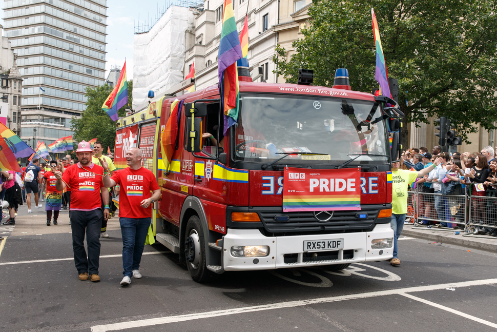 "Two firefighters in red ""LFB PRIDE"" tshirts walk in a parade alongside a fire engine. The fire engine is decorated with at least five rainbow flags."