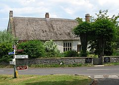 Thatched stone house surrounded by trees. In the foreground a road junction and sign.