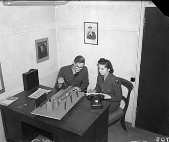 """Royal Air Force Film Production Unit - The film director and WAAF continuity girl discuss the set-up of a shot in a scene at a railway station from """"Journey Together"""" at No. 1 RAFFPU at RAF Stanmore Park, Middlesex"""