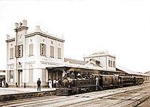 Fotografia de uma locomotiva a vapor puxando carros de passageiros e sentando-se na plataforma de fora de um grande edifício da estação