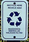 A rectangular sign with rounded corners, text about recycling, and the recycling symbol