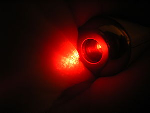 English: Red diode laserbeam on skin. Never lo...
