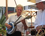 Man playing a four-string banjo.
