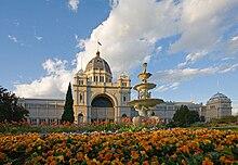 Edifício branco ornamentado com uma cúpula elevada no meio, com uma fonte dourada e flores alaranjadas na frente