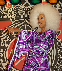 RuPaul holding a microphone and pointing