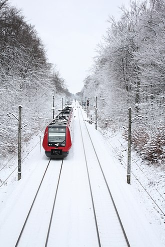 Hareskov station - S-train drives through the snowy Hareskoven forest. The station can be seen in the background.