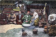 Photographie colorisée. Plusieurs personnes se trouvent à l'intérieur d'une yourte.
