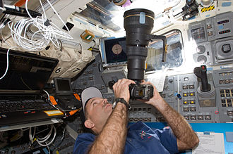 STS-125 - John Grunsfeld uses a Nikon D2X with telephoto lens at an overhead window on the aft flight deck during flight day three activities.