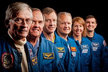 Photograph of Young and Crippen standing in a row with the crew of STS-135