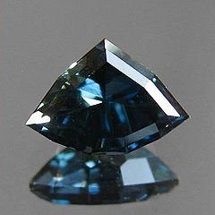 A custom shield cut sapphire from Rock Creek, Montana in deep blue with a slight green undertone or zoning.