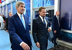 A photograph of John Kerry (left) and Leonardo DiCaprio both dressed in suits and looking away from the camera